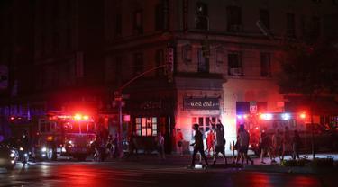 Pejalan kaki menyeberang jalan dekat kendaraan tanggap darurat saat pemadaman listrik di New York, AS, Sabtu (13/7/2019). Pemadaman listrik melanda sekitar 42 ribu pelanggan di Kota New York. (AP Photo/Michael Owens)