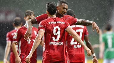 Striker Bayern Munchen, Robert Lewandowski, melakukan selebrasi bersama Jerome Boateng usai membobol gawang Werder Bremen pada laga Bundesliga di Weserstadion, Bremen, Selasa (16/6/2020). Bayern Munchen menang dengan skor 1-0 atas Werder Bremen. (AP/Martin Meissner)