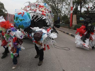 Aktivis pemerhati lingkungan mengarak monster plastik saat aksi Tolak Penggunaan Plastik Sekali Pakai di Pelabuhan Sunda Kelapa, Jakarta, Sabtu (20/7/2019). Monster plastik itu berupa rangka berbentuk ikan jenis anglerfish yang ukurannya sebesar mobil sampah. (Liputan6.com/Herman Zakharia)