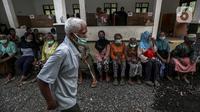 Pengungsi Gunung Merapi mengenakan masker di lokasi pengungsian di Desa Glagaharjo, Sleman, Jawa Tengah, Rabu (18/11/2020). Kondisi Gunung Merapi yang memasuki level siaga membuat beberapa desa dengan radius 5 Km dari puncak Gunung Merapi mengungsikan penduduknya. (Liputan6.com/Johan Tallo)