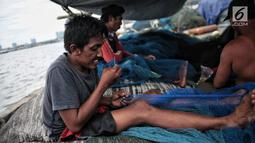 Sejumlah nelayan memperbaiki jaring di Pelabuhan Muara Angke, Jakarta, Kamis (27/12). Libur melaut dimanfaatkan nelayan untuk memperbaiki kapal dan jaring. (Liputan6.com/Faizal Fanani)