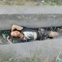 Pria ini dikira sudah tak bernyawa dan dibiarkan tidur di selokan penuh sampah. (Sumber Foto: vial4real)
