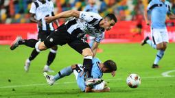 Bek Lazio, Stefan Radu, berebut bola dengan penyerang Udinese, Kevin Lasagna, pada laga lanjutan Serie A pekan ke-33 di Dacia Arena, Kamis (16/7/2020) dini hari WIB. Lazio bermain imbang 0-0 atas Udinese. (AFP/Miguel Medina)