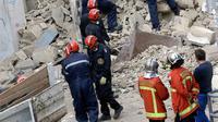 Petugas pemadam kebakaran terlihat berada dekat bangunan yang runtuh di kota Marseille, selatan Prancis, Senin (5/11). Kuat dugaan insiden runtuhnya bangunan tersebut karena sudah tua dan dalam kondisi rusak. (AP/Claude Paris)