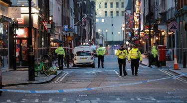 Polisi memblokir jalan menyusul penemuan bom Perang Dunia II di kawasan Soho, London, Inggris, Senin (3/2/2020). Polisi mengevakuasi warga yang berada di kafe, restoran, pub, dan kantor radius beberapa blok dari lokasi penemuan bom. (AP Photo/Frank Augstein)