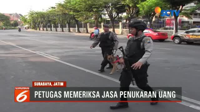 Dengan membawa senjata laras panjang dan satu ekor K-9, aparat kepolisian Polrestabes Surabaya melakukan  pemeriksaan uang rupiah baru.