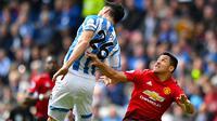 Pemain Huddersfield Town, Christopher Schindler berebut bola dengan penyerang sayap Manchester United, Alexis Sanchez pada pekan ke-37 Liga Inggris di John Smith's Stadium, Minggu (5/5/2019). MU gagal ke Liga Champions musim depan setelah ditahan Huddersfield Town 1-1. (Anthony Devlin/PA via AP)