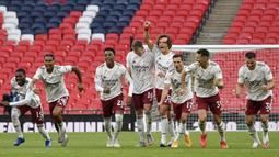 Para pemain Arsenal bereaksi saat rekan setimnya Pierre-Emerick Aubameyang mencetak gol penalti kemenangan dalam adu penalti pada laga Community Shield  di stadion Wembley di London, Sabtu, (29/8/2020). (Justin Tallis / Pool via AP)