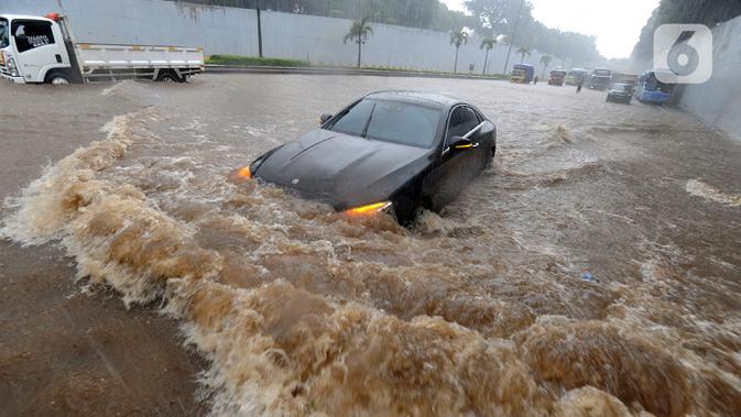 Mobil menerjang banjir yang menggenangi Jalan Tol JORR di kawasan TB Simatupang, Jakarta Selatan, Sabtu (20/2/2021). Banjir terjadi akibat luapan Kali Serua yang berada di pinggir jalan tol. (merdeka.com/Arie Basuki)
