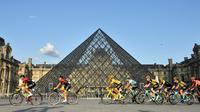 Pebalap Kolombia Egan Bernal (tengah) melewati museum piramida Louvre saat mengikuti Tour de France 2019, Paris, Prancis, Minggu (28/7/2019 ). Tour de France 2019 dimulai dari Rambouillet dan berakhir di Paris. (Julien de Rosa/Pool Photo via AP)