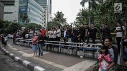Sejumlah warga melihat konvoi kemenangan Persija Jakarta merayakan keberhasilan menjadi juara Piala Presiden 2018 di kawasan Bundaran HI, Minggu (18/2). Konvoi dimulai dari Stadion Utama Gelora Bung Karno menuju Balai Kota. (Liputan6.com/Faizal Fanani)