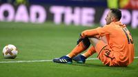 Kiper Arsenal, David Ospina duduk di lapangan pada akhir laga leg kedua semifinal Liga Europa melawan Atletico Madrid di Wanda Metropolitano, Kamis (3/5). Arsenal tersingkir dari Liga Europa setelah kalah 0-1. (AFP/PIERRE-PHILIPPE MARCOU)