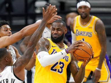 Pebasket Los Angeles Lakers, LeBron James, berebut bola dengan pebasket San Antonio Spurs, Lonnie Walker dan Keldon Johnson pada laga NBA di AT&T Center, Kamis (31/12/2020). LA Lakers menang dengan skor 121-107. (AP/Eric Gay)