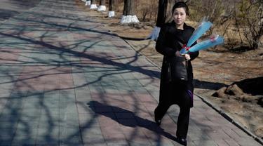 Seorang wanita membawa bunga saat menandai Hari Perempuan Internasional di Pyongyang, Korea Utara, Jumat (8/3). Hari Perempuan Internasional jatuh pada tanggal 8 Maret setiap tahunnya. (AP Photo/Dita Alangkara)