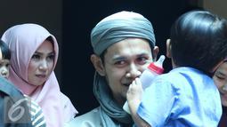 Ustadz Guntur Bumi (UGB) menggendong anaknya usai mengisi sebuah acara di kawasan Tendean, Jakarta, Rabu (16/11). UGB mengaku kurang komunikasi kepada istrinya dan kini berusaha untuk memperbaikinya. (Liputan6.com/Herman Zakharia)