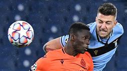 Gelandang Lazio, Sergej Milinkovic-Savic, berebut bola dengan bek Club Brugge, Odilon Kossounou, pada laga Grup F Liga Champions di Olympic Stadium, Rabu (9/12/2020) dini hari WIB. Lazio bermain imbang 2-2 melawan Club Brugge. (AFP/Tiziana Fabi)