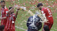 Pelatih Bayern, Carlo Ancelotti menerima seiraman bir oleh Juan Bernat saat perayaan gelar juara Bundesliga 2016-2017 di  Allianz Arena stadium, Munich, (20/5/2017).  (AP/Matthias Schrader)