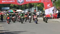 Para pebalap melewati garis start pada Honda Dream Cup 2019, di Sirkuit Banjarbaru, Kalimantan Selatan, Minggu (14/7/2019).  (FOTO / Nurfahmi Budiarto)