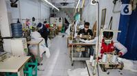 Pekerja menyelesaikan pembuatan pakaian untuk Alat Pelindung Diri (APD) tenaga medis di kawasan Penggilingan, Jakarta, Kamis (26/3/2020). Harga yang dijual untuk APD bekisar antara Rp 45.000 untuk jenis pakaian sekali pakai dan Rp 75.000 untuk pakaian yang bisa dicuci. (Liputan6.com/Faizal Fanani)