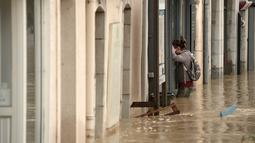 Seorang wanita melintasi banjir setinggi paha di dekat sebuah toko setelah hujan lebat di Salies-de-Bearn, Perancis barat daya (13/6). (AFP Photo/Iroz Gaizka)