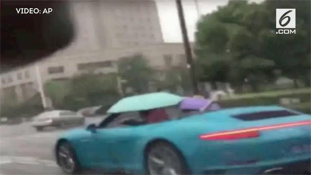 Diduga atap mobil tidak bisa dibuka, seorang pengendara mobil sport di China malah membuka payung dikala hujan.