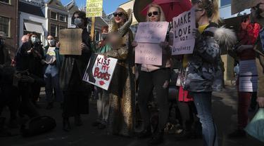 Para pekerja seks membawa plakat memprotes perlakuan dan stigma yang tidak setara selama demonstrasi di Den Haag, Belanda, Selasa (2/3/2021). Mereka berdemonstrasi di luar parlemen dalam protes terhadap penguncian keras virus corona oleh pemerintah. (AP Photo/Patrick Post)