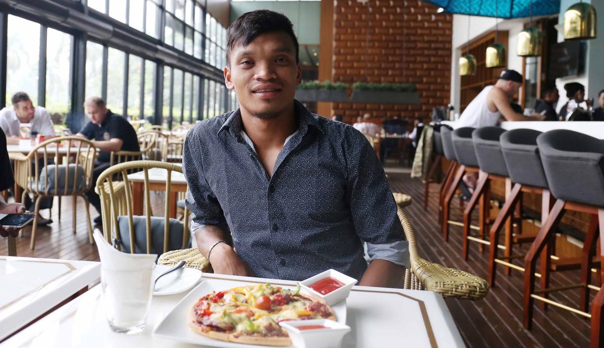 Pemain Sriwijaya FC, Ferdinand Sinaga menikmati Piza usai menjalani sidang Komisi Disiplin di Hotel Century, Senayan. Jakarta, Jumat (4/12/2015). (Bola.com/Nicklas Hanoatubun)