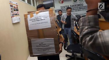 Petugas Bawaslu Jakarta Pusat membawa kardus berisi form C1 Pemilu yang diamankan di Gedung Bawaslu Jakarta Pusat, Senin (6/5/2019). Pihak Bawaslu mengatakan masih akan melakukan investigasi dan pemeriksaan terhadap temuan form C1 dari sejumlah daerah itu. (Liputan6.com/Helmi Fithriansyah)