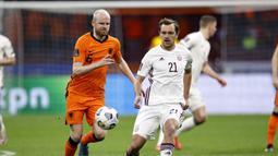 Gelandang Belanda, Davy Klaassen (kiri) berebut bola dengan gelandang Latvia, Kriss Karklins dalam laga Kualifikasi Piala Dunia 2022 Zona Eropa Grup G di Johan Cruijff Arena, Amsterdam, Sabtu (27/3/2021). Belanda menang 2-0 atas Latvia. (AFP/Maurice van Steen/ANP)