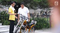 Presiden Joko Widodo atau Jokowi (kiri) menunjukkan motornya kepada Menteri Perindustrian Airlangga Hartarto saat olahraga bersama di Istana Bogor, Sabtu (24/3). Jokowi mengaku Airlangga ingin melihat motor miliknya. (Liputan6.com/Pool/Biro Pers Setpres)