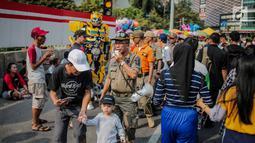 Petugas Satpol PP melakukan sosialisasi saat menertibkan PKL di kawasan car free day (CFD), Bundaran HI, Jakarta, Minggu (4/8/2019). Penertiban dilakukan karena keberadaan PKL membuat tidak nyaman pengunjung CFD yang ingin berolahraga, berorasi, atau sekadar jalan-jalan. (Liputan6.com/Faizal Fanani)