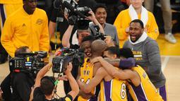 Para pemain Los Angeles Lakers memeluk Kobe Bryant usai pertandingan antara Lakers melawan Utah Jazz di Staples Center, AS, (13/4).Pertandingan kali  ini merupakan yang terakhir bagi Kobe Bryant. (Gary A. Vasquez-USA TODAY Sports)