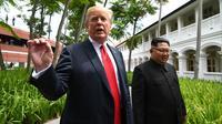 Presiden AS Donald Trump (kiri) berbicara kepada media saat berjalan dengan Pemimpin Korea Utara Kim Jong-un selama istirahat perundingan AS-Korea Utara di Hotel Capella, Pulau Sentosa, Singapura, Selasa (12/6). (Anthony Wallace/Pool/AFP)