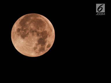 Gerhana bulan total terlihat di kota Semarang, Sabtu (28/7) dini hari. Gerhana bulan total tahun ini merupakan fenomena langka karena terjadi selama 1 jam 43 menit atau merupakan gerhana terlama yang terjadi di abad ini. (Liputan6.com/Gholib)