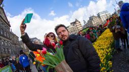 Sepasang pengunjung berswafoto saat orang-orang memetik tulip gratis pada Hari Bunga Tulip Nasional di Dam Square, Amsterdam, 18 Januari 2020. Hari Bunga Tulip Nasional ini menandai pembukaan musim bunga tulip untuk industri bunga Belanda.  (AP Photo/Peter Dejong)