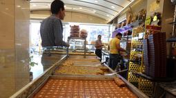 Seorang pria membeli penganan manis saat bulan suci Ramadan di sebuah toko di Baghdad, Irak, pada 3 Mei 2020. (Xinhua/Khalil Dawood)