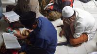 Jamaah membaca Alquran di Masjid Kauman Semarang, Senin (29/5). Setiap selepas sholat dzuhur hingga menjelang ashar masjid ini selalu dipenuhi banyak orang untuk mengikuti pengajian Al qur'an 30 juz. (Liputan6.com/Gholib)