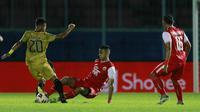 Bek Persija Jakarta, Otavio Dutra (tengah) menghadang pemain Bhayangkara Solo FC, Sani Rizki Fauzi, pada laga Piala Menpora 2021 di Stadion Kanjuruhan, Malang, Rabu (31/3/2021). Persija Menang dengan skor 2-1. (Bola.com/M Iqbal Ichsan)