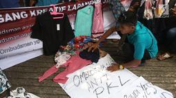 Pedagang kaki lima (PKL) dari Forum Pedagang Kreatif Lapangan Jatibaru menggelar dagangan mereka di depan kantor Ombudsman, Jakarta, Selasa (3/4). Aksi ini untuk mempertanyakan laporan Ombudsman mengenai penataan Tanah Abang. (Liputan6.com/Arya Manggala)