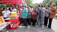 Pegawai antri untuk membeli minyak goreng murah Bazar Rakyat di lapangan parkir Kemenlu, Jakarta. (19/08). Sekitar 2.000 liter minyak goreng kemasan seharga Rp 7.000 per liter disalurkan bagi keluarga besar Kemenlu. (Liputan6.com/Angga Yuniar)