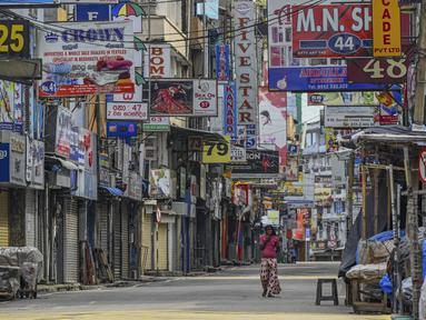 Seorang perempuan melintas di sepanjang jalan yang sepi setelah pemerintah memberlakukan pembatasan perjalanan dan lockdown akhir pekan di Kolombo, Sri Lanka, Sabtu (22/5/2021). Sri Lanka pada Jumat, 21 Mei mencatat 3.547 kasus harian corona Covid-19. (Ishara S. KODIKARA/AFP)