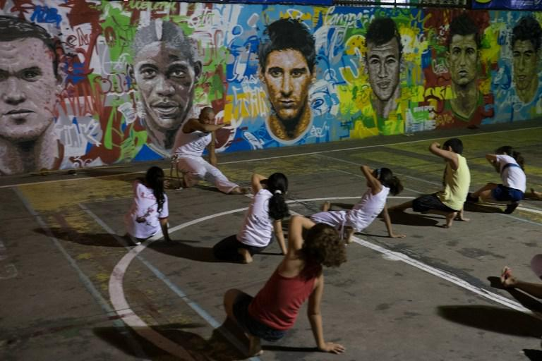 Anak-anak sedang berlatih seni bela diri khas Brasil Capoeira di dekat tembok lukisan wajah pemain top dunia, Brasil, Rabu (21/05/2014) (AFP PHOTO/Yasuyoshi CHIBA).