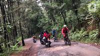 Pengunjung melintasi akses jalan di kawasan wisata Gunung Bunder, Bogor, Jawa Barat, Minggu (15/11/2020). Meskipun pandemi covid-19 belum berakhir, namun sejumlah lokasi wisata mulai dipadati pengunjung dengan tetap menerapkan protokol kesehatan. (Liputan6.com/Immanuel Antonius)