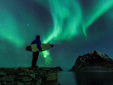 Seorang surfer melihat Cahaya Utara atau aurora borealis di Utakleiv, Norwegia utara (9/3). Aurora ini adalah sebuah peristiwa langit yang cantik berupa pancaran cahaya yang menyala-nyala di atmosfer sekitar lingkaran Arktik. (AFP/Olivier Morin)