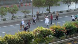 Massa melempar batu ke arah petugas kepolisian dari jalan tol dalam kota saat bentrok massa di kawasan Slipi, Jakarta, Rabu (22/5/2019). Jalan tol  dalam kota sempat ditutup sekitar setengah jam, dan massa dihalau petugas ke arah kemanggisan. (merdeka.com/Arie Basuki)