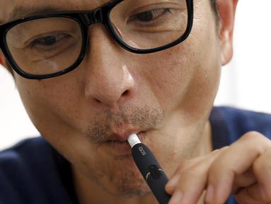 Salah satu pelanggan saat mencoba iQOS di sebuah toko, Tokyo , Jepang , (3/3).  iQOS merupakan sebuah alat pemanas untuk sebatang rokok dengan menggunakan listrik. (REUTERS / Toru Hanai)