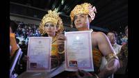 Sepasang pengantin memperlihatkan surat nikah saat mengikuti Resepsi Penikahan Massal Pengantin se-Jabodetabek di Istora Senayan, Jakarta, Rabu (28/1/2015). (Liputan6.com/Herman Zakharia)