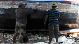 Pekerja menyelesaikan proses perbaikan kapal nelayan di pesisir Marunda, Jakarta, Selasa (22/10/2019). Jasa perbaikan kapal nelayan merupakan salah satu mata pencaharian utama warga pesisir Marunda selain mencari ikan di laut. (merdeka.com/Iqbal Nugroho)