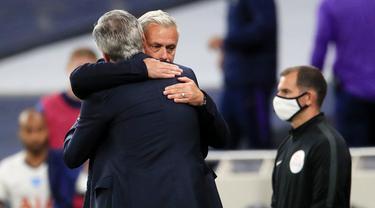 Pelatih Tottenham Hotspur, Jose Mourinho, berpelukan dengan pelatih Everton, Carlo Ancelotti, pada laga Premier League, Senin (6/7/2020). Mourinho melanggar aturan jarak sosial demi memeluk Carlo Ancelotti yang merupakan idolanya. (AFP/Adam Davy)