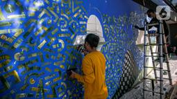 Seniman mural komunitas Converse All Stars melukis dinding Institut Perancis Indonesia (IFI) di Jalan MH. Thamrin, Jakarta, Rabu (2/12/2020). Para seniman mengkampanyekan upaya pembersihan udara perkotaan dengan menanam pohon. (Liputan6.com/Faizal Fanani)